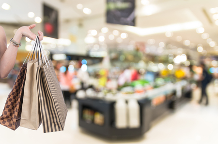 shoping: Holding shoping bags by hand on salad bar store blur with bokeh background, Miscellaneous Product shelf Stock Photo