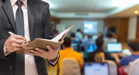 Zakenman het schrijven van de nota boek op de Kort wazig foto van conferentiezaal of seminar kamer met genodigde achtergrond