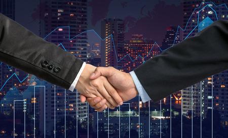 comercio: Sacudida de la mano entre el empresario en el gráfico de comercio en el paisaje urbano en el mapa del mundo y de la noche, concepto financiero de negocios Foto de archivo
