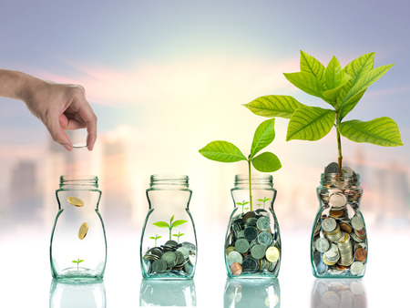 economy growth: Hand putting mix coins and seed in clear bottle on cityscape photo blurred cityscape ,Business investment growth concept Stock Photo