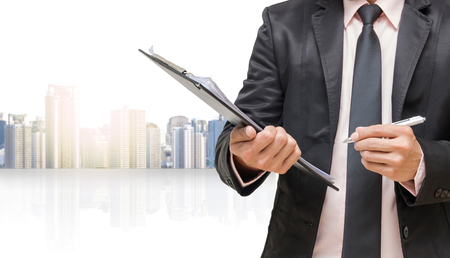 Businessman pointing or touching on cityscape blurred background,Business concept