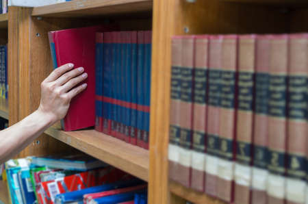 selecting: closeup hand selecting book from a bookshelf in library Stock Photo