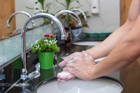 switcher: Hand washing with Chrome faucet over the washbasin in modern bathroom