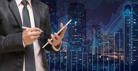 Geschäftsmann mit der Tablette auf Handels Grafik auf dem Stadtbild in der Nacht und Weltkarte Hintergrund, Geschäftsfinanzkonzept