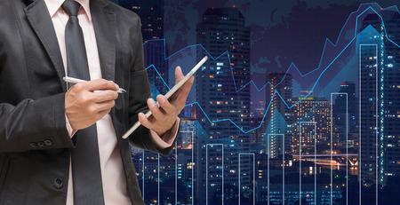 empresario: Hombre de negocios usando la tableta en el gr�fico de comercio en el paisaje urbano en el fondo del mapa del mundo y de la noche, concepto financiero de negocios Foto de archivo