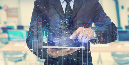 hombre de negocios: Doble exposición de negocios usando la tableta con el paisaje urbano y el gráfico financiera que tiene la tierra y el mapa del mundo sobre fondo borrosa equipo