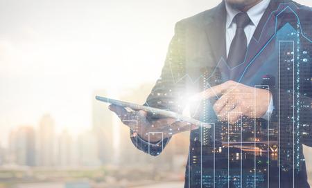ejecutivo en oficina: Doble exposici�n de negocios usando la tableta con el paisaje urbano y gr�fico financiero en el fondo borrosa edificio, concepto de negocio de comercio