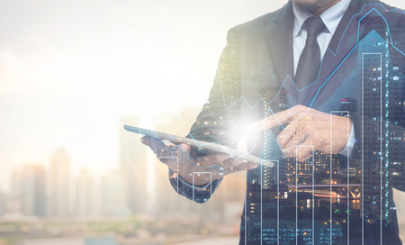 finance: Double exposure of businessman using the tablet with cityscape and financial graph on blurred building background, Business Trading concept