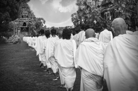 nuns: Many unidentified Buddhist nuns in white suit walking for celebrate Buddhist Sabbath at Angkor wat in Siem Reap, Cambodia black and white tone