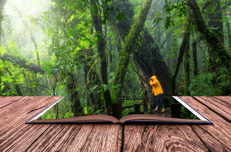 green environment: conceptual book image of Traveller taking photo at Beautiful rain forest