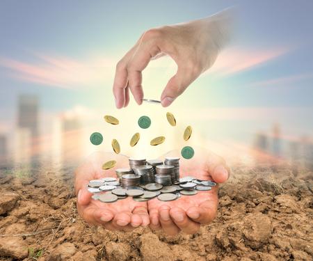 ganancias: Mano que pone una moneda en la pila de monedas sobre las manos en el arroz presentó y el paisaje urbano de fondo borroso, la inversión empresarial y el concepto de ahorro Foto de archivo