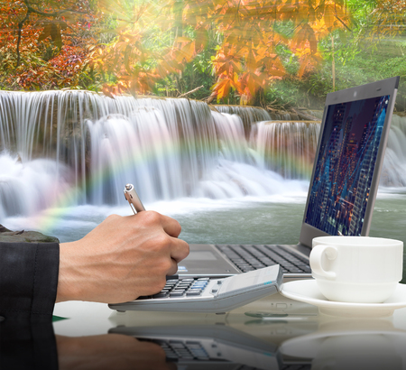 Businessman working with the laptop on Beautiful waterfall in the deep forest with rainbow,Business financial concept