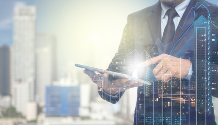hombre de negocios: Doble exposición de negocios usando la tableta con el paisaje urbano y gráfico financiero en el fondo borrosa edificio, concepto de negocio de comercio