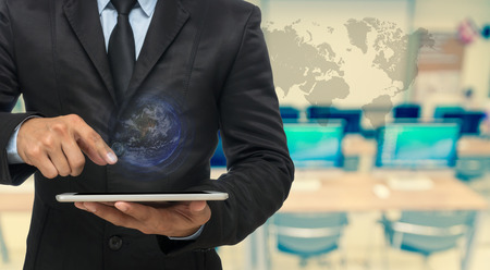 computer system: Businessman using the tablet on Abstract blurred photo of empty computer room with earth and world map,Elements of this image furnished by NASA, education and business concept