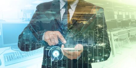 Double exposure of businessman using the tablet with cityscape and financial graph which have earth and world map on computer blurred background, Elements of this image furnished by NASA, education and business concept