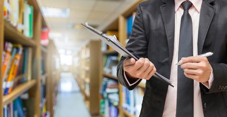 biblioteca: Empresario escribir la almohadilla de archivos en la foto borrosa abstracta del fondo de la biblioteca