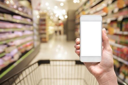 スーパー マーケットにモバイルのスマート フォンを持っている女性の手が、ビジネス概念の背景をぼかし