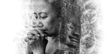 disintegration: Double exposure and Disintegration of old woman praying with face of Bayon Temple at Angkor Thom