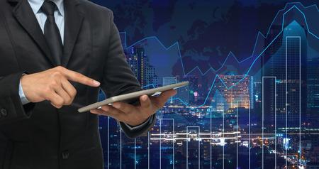 hombre de negocios usando la tableta en el gráfico de comercio en el paisaje urbano en el fondo del mapa del mundo y de la noche, concepto financiero de negocios Foto de archivo