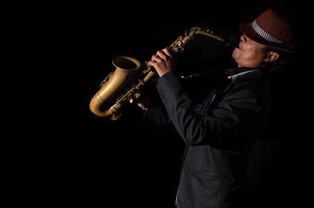 saxofón: Un jugador de saxofón en un fondo oscuro, el tono blanco y negro Foto de archivo