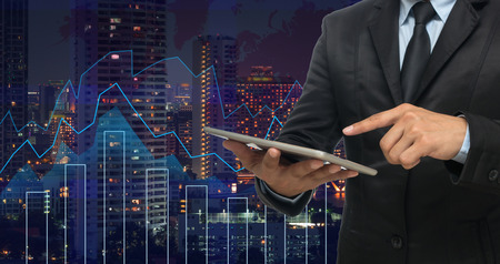 financial market: businessman using the tablet on Trading graph on the cityscape at night and world map background,Business financial concept Stock Photo