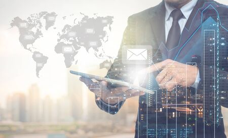 Double exposure of businessman using the tablet with cityscape and financial graph on blurred building with world map and mail background, Elements of this image furnished by NASA Banco de Imagens