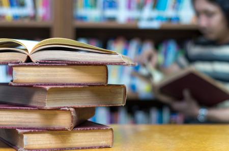 biblioteca: viejo libro sobre la mesa en la biblioteca con el hombre leyendo el fondo de libros Foto de archivo