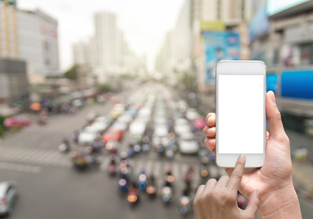 hand jam: Female hand holding mobile smart phone on abstract Blurred photo of traffic jam with rush hour Stock Photo