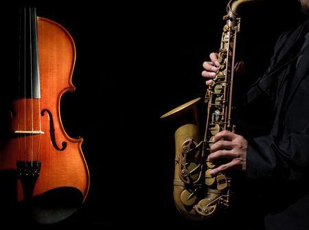 Closeup saxophone in player action with Violin orchestra musical instruments on black background