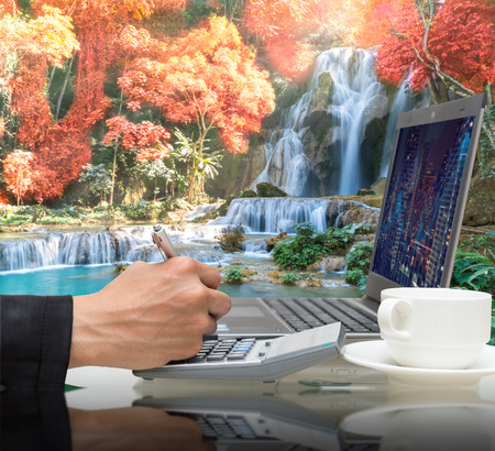 waterfall in the forest: Businessman working with the laptop on Beautiful waterfall in the deep forest with rainbow,Business financial concept