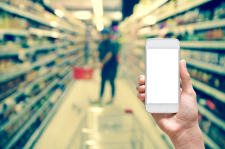 store: Female hand holding mobile smart phone touch screen on Abstract blurred photo of store with trolley in department store bokeh background Stock Photo