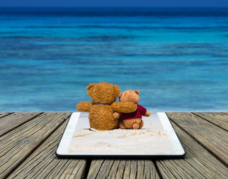 Conceptual image of a tablet on two teddy bear brown color sitting on the beautiful beach with blue sea and sky