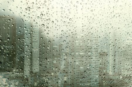 waterdrops: Waterdrops on a glass surface windows with closeup cityscape background