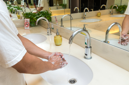 switcher: Hand washing with Chrome faucet over the washbasin in modern toilet