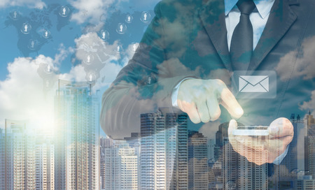 reverberation: Double exposure of businessman using the tablet for sending the email on world map and cityscape background, business concept,Elements of this image furnished by NASA