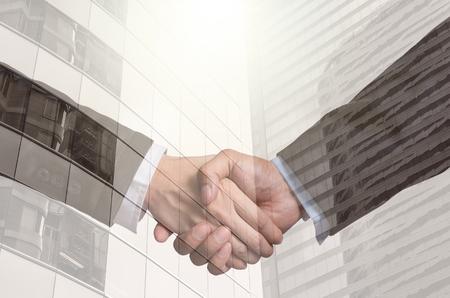 apreton de manos: doble apretón de manos entre el hombre de negocios en la exposición Fondo moderno edificio de cristal