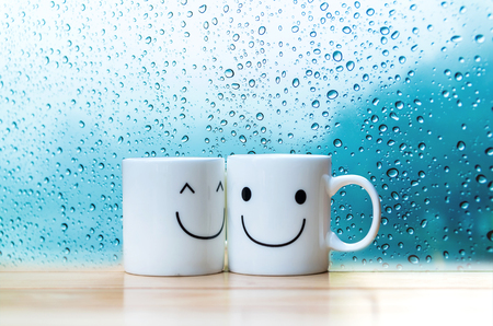 Two happy cups on the wood table with a glass surface windows, about love concept Standard-Bild