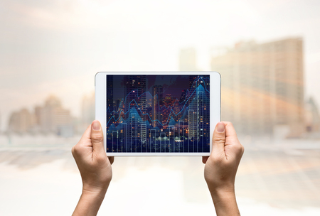 show business: female hands holding a tablet that show business trading graph on cityscape blurred background,business investment concept