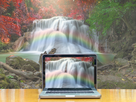 notebook computer: Conceptual image of a computer laptop on Beautiful waterfall with soft focus and rainbow in the forest Stock Photo