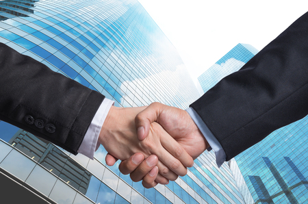 shake hand: Hand shake between a businessman on Modern glass building background, Business agreement concept