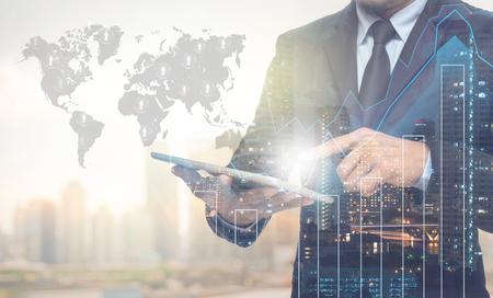 hombre de negocios: Doble exposición de negocios usando la tableta con el paisaje urbano y gráfico financiero en la construcción borrosa con mapa del mundo y la gente logotipo de fondo, elementos de esta imagen proporcionada por la NASA