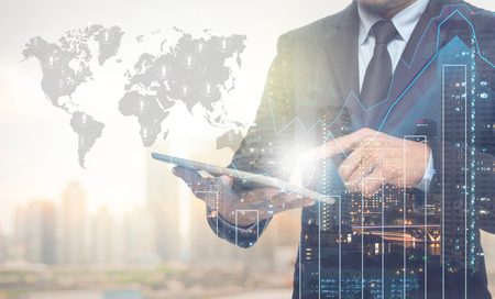 leadership: Double exposure of businessman using the tablet with cityscape and financial graph on blurred building with world map and people logo background, Elements of this image furnished by NASA