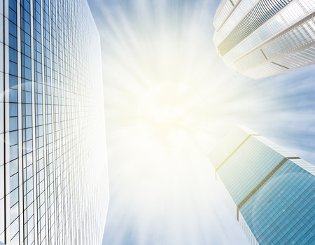 reverberation: Modern business building glass of skyscrapers on blue sky background with sun light, Business concept of architecture
