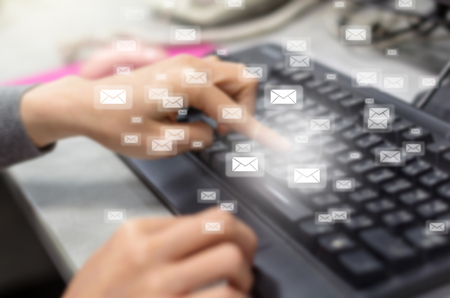 spam mail: Many e-mail over the finger pressing the computer keyboard blurred background, business technology concept Stock Photo
