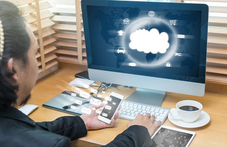 nas: Businessman working at Workplace with office accessories send the e-mail and cloud technology on wooden table Stock Photo