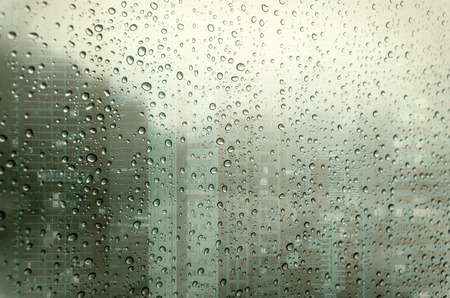 Waterdrops on a glass surface windows with closeup cityscape background