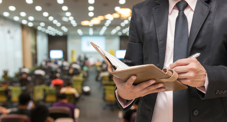 podium: Businessman using the tablet on the Abstract blurred photo of conference hall or seminar room with attendee background Stock Photo