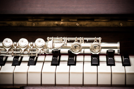 flute structure: Closeup Flute on the keyboard of piano, musical instrument, vintage tone