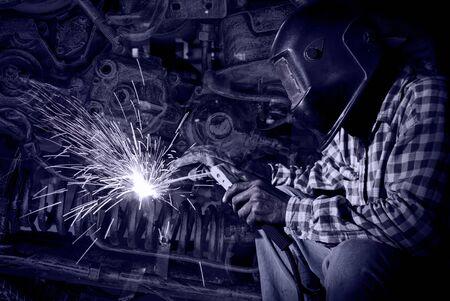 welding: welder at work with old machine steel background, industry concept Stock Photo