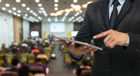 会議ホールやセミナー ルーム参加者のバック グラウンドの抽象的なぼやけた写真にタブレットを使用して実業家